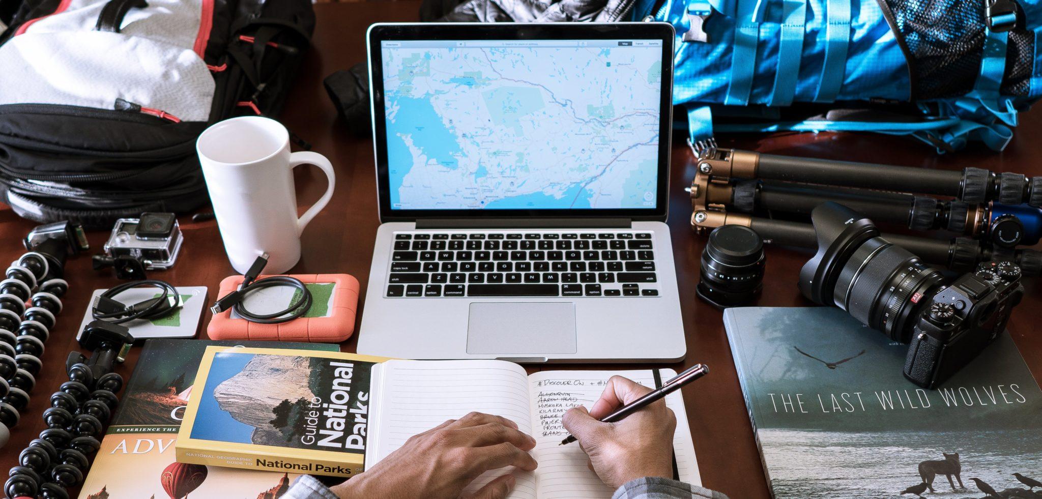 uma mesa com objetos como notebook, uma caneca, uma câmera, livros, um tripé, e no canto inferior vemos as mãos de uma pessoa escrevendo em um caderno