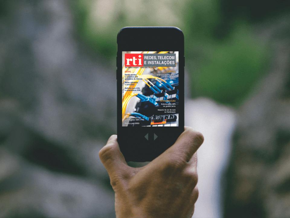 mão segurando celular com capa da revista rti na tela